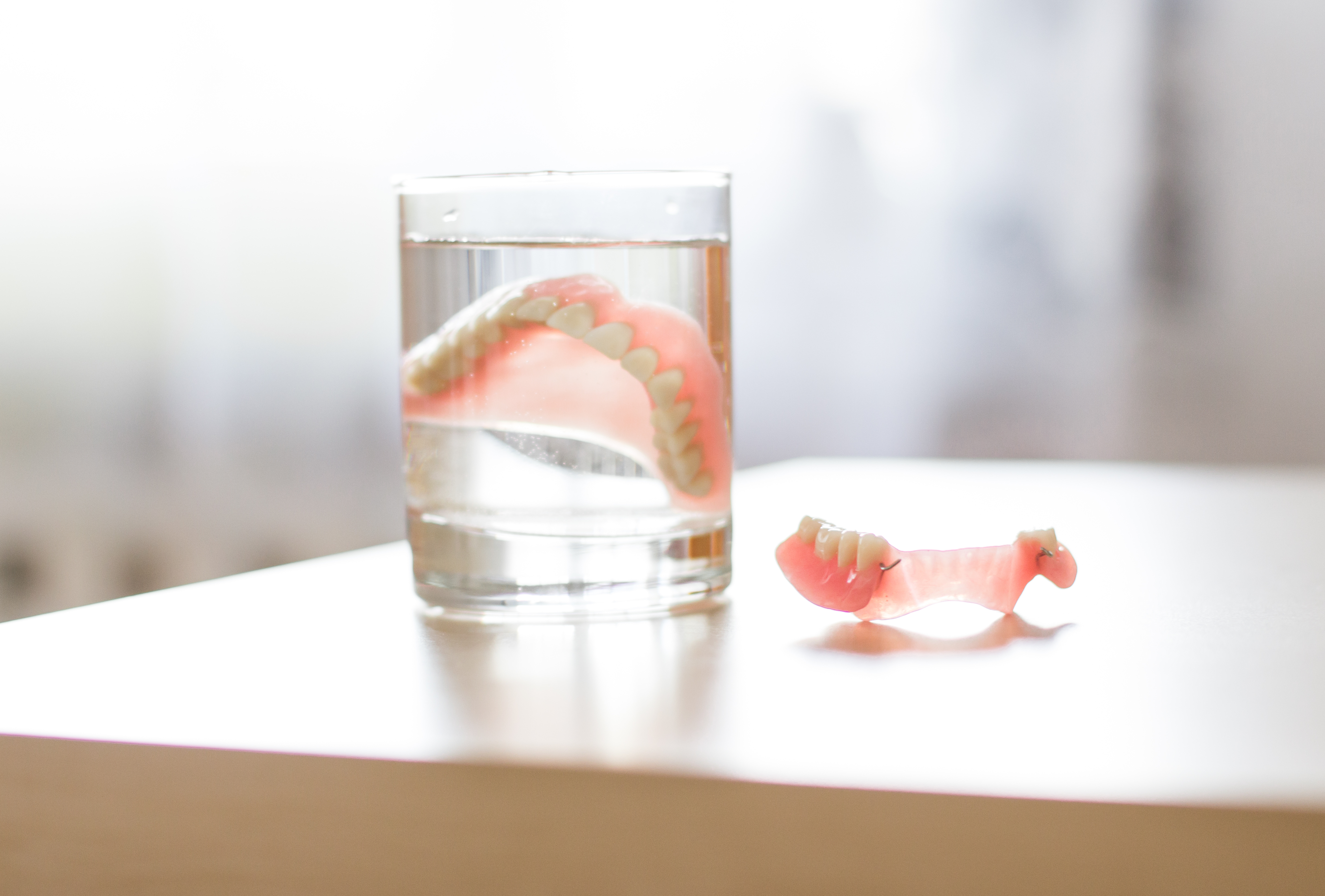 Traditionals dentures in Anchorage soaking in glass
